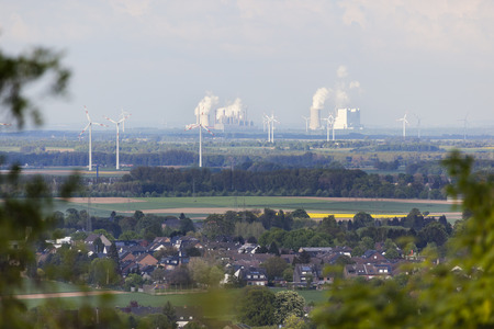 rhine westphalia: Long distance view over rural landscape to steaming coal-fired power stations, framed by branches and leafs of some trees.