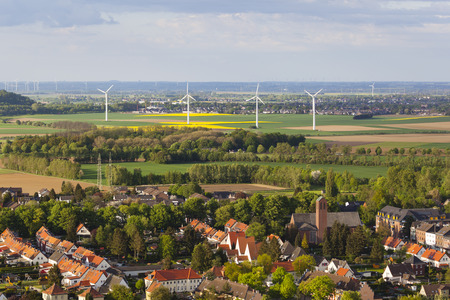 Flat west German landscape near Aachen and Herzogenrath with wind turbines behind a small village.