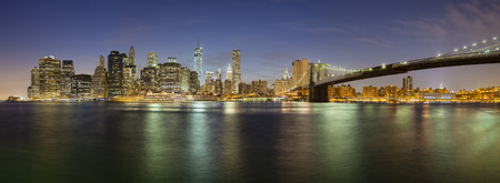 The Manhattan skyline in New York City at night including the new One World Trade Center and Brooklyn Bridge.