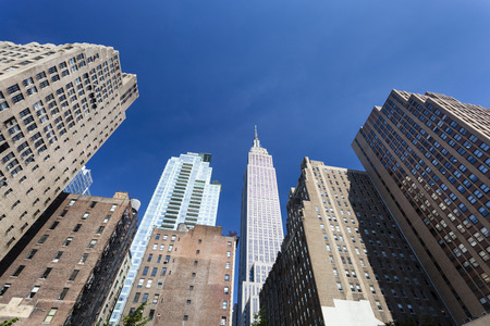 The Empire State Building in New York with deep blue sky framed by other skyscrapers