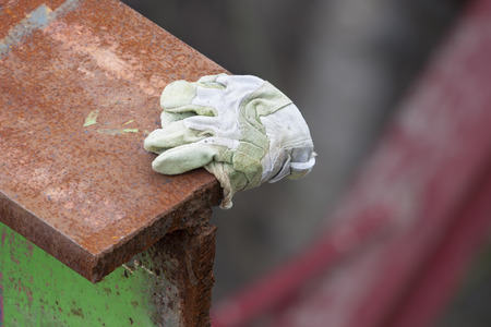 steel girder: A cut rusty steel beam with a work glove covering a sharp edge