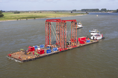 deconstruction: Industrial carrying platform pushed by a push boat on rhine river, Germany. The platform is used as a swimming support for bridge deconstruction.