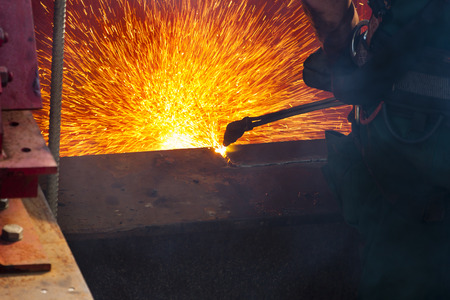 steel beam: Worker cutting a steel beam of an old bridge with sparks flying around.