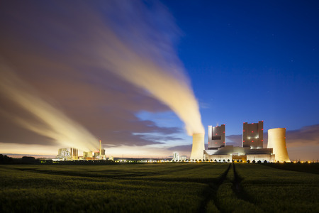 powerplants: Two steaming coalfired power stations behind a field at night