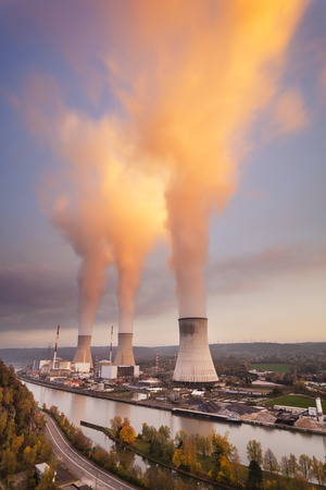 nuclear power station: A large nuclear power station by a river during sunset Stock Photo