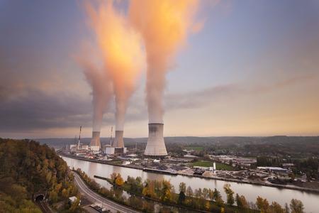 日没時に川で大型の原子力発電所