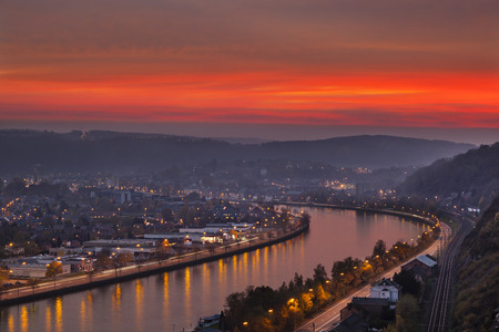 meuse: View over the Meuse to Huy in Belgium during a fiery red sunset