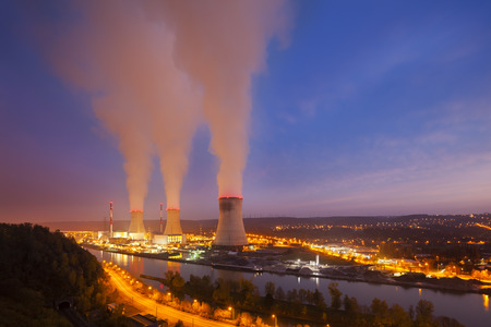 nuclear power station: A large nuclear power station by a river with night blue sky