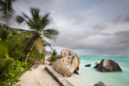 d'argent: Dark clouds over the beach Anse Source DArgent in La Digue, Seychelles with scenic granite rocks and palm trees