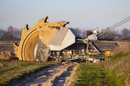 coal mine: A giant Bucket Wheel Excavator at work in a lignite pit mine with a dirt road leading to it in the foreground