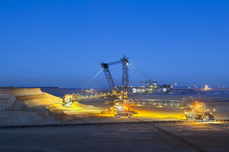 lignite: A giant Bucket Wheel Excavator at work in a lignite pit mine at night Stock Photo