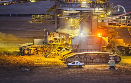 夜のピックアップ トラックの横にある巨大なバケット ホイール掘削機の Caterpillats 詳細ビュー
