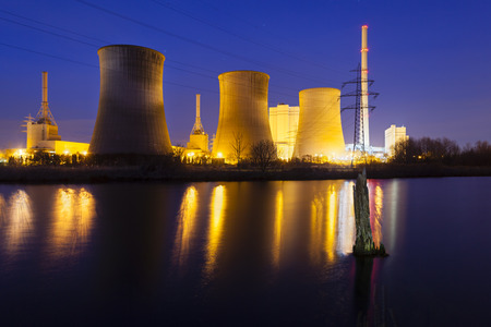 power industry: A coal-fired power station in river landscape with dead trees at night Stock Photo