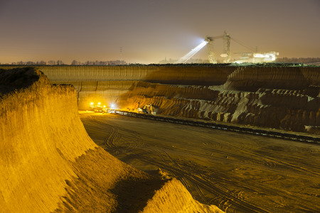 lignite: A steep lignite pit mine wall illuminated at night with an excavator in the background