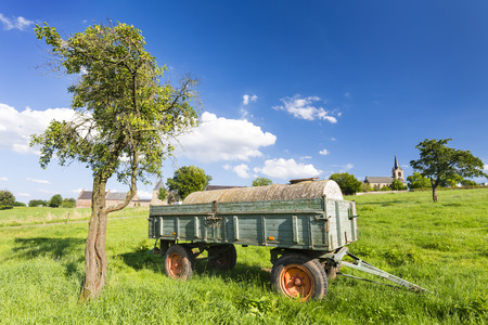 old church: An old fertilizer trailer on a green meadow with a village in the background and blue sky. Stock Photo