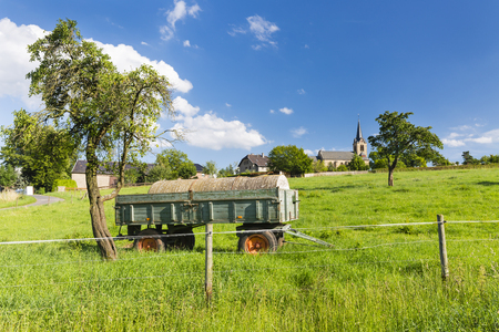 An old fertilizer trailer on a green meadow with a village in the background and blue sky. Stock Photo