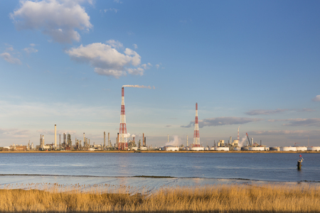 flare stack: A large oil refinery in the harbor of Antwerp, Belgium with blue sky and warm evening light.