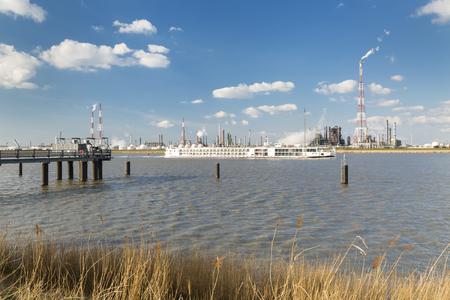 destilacion: Una gran refinería con tanques de almacenamiento de gas en el puerto de Amberes, Bélgica, con un montón de torres de destilación y un embarcadero en el primer plano. Un barco de pasajeros que pasa por el río Escalda.