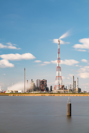 destilacion: Tiro de larga exposición de una refinería con antorcha de altura en el puerto de Amberes, Bélgica, con un montón de torres de destilación.