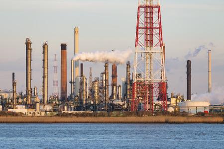 destilacion: Una gran refiner�a de petr�leo con la antorcha en el puerto de Amberes, B�lgica, con un mont�n de torres de destilaci�n y la luz c�lida noche.