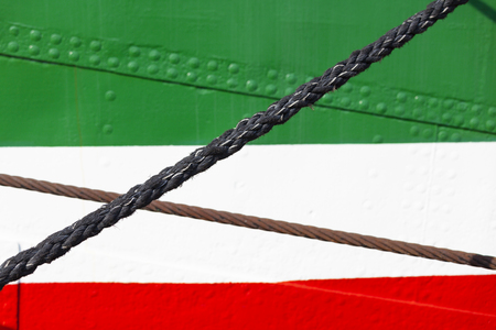 hull: A colorful ship hull in green, white and red with some ropes. Stock Photo