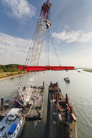 deconstruction: Floating crane carrying girder platform to support a bridge deconstruction on Rhine river, Germany