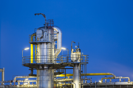 tele up: Detail of a distillation tower of a chemical plant and refinery with night blue sky and illumination.