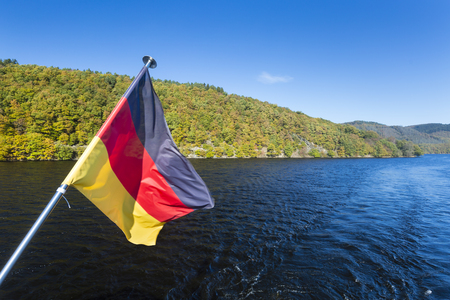 german flag: German flag on a boat on Lake Rursee with blue sky and sunlight in summer.
