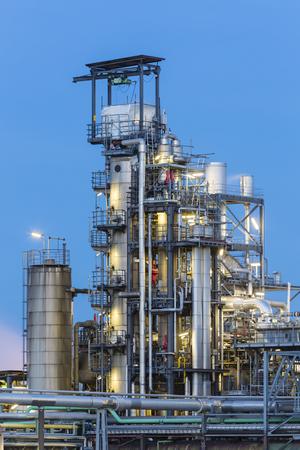 destilacion: Detalle de las torres de destilación en una planta química y refinería con la noche el cielo azul.