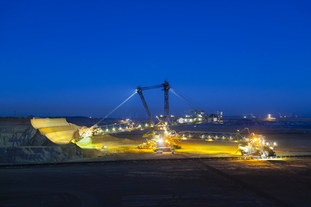 lignite: A giant Bucket Wheel Excavator at work in a lignite pit mine at night with some motion blur Stock Photo