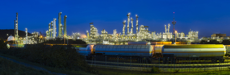 chemical plant: Panoramic view of a chemical plant and refinery with night blue sky and illumination, some freight trains in the foreground.