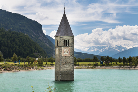 The old church tower of Reschen in the reservoir Lake Reschen, Italy Stock Photo