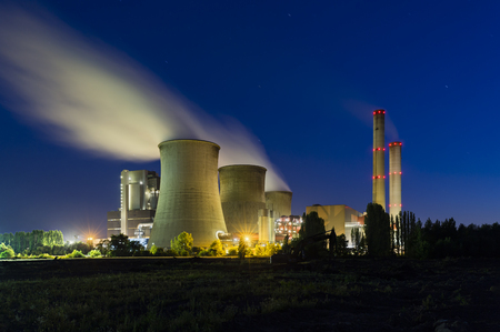 A large coal-fired power plant at night with a lot of steam and deep blue sky.