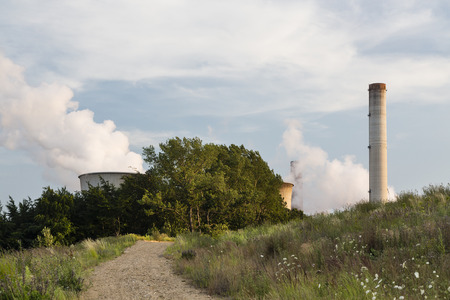 hill station tree: A large coal-fired power plant behind a hill with a dirt road leading towards it. Stock Photo