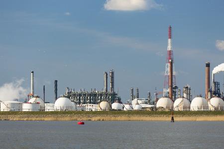 destilacion: Una gran refinería con tanques de almacenamiento de gas en el puerto de Amberes, Bélgica, con un montón de torres de destilación.