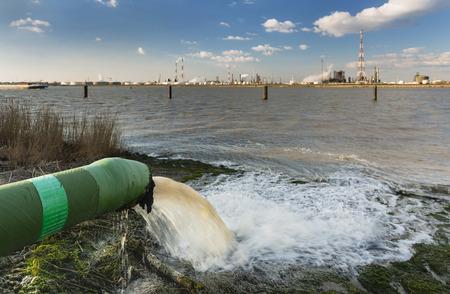 Una tubería de aguas residuales y una gran refinería de petróleo en el puerto de Amberes, Bélgica con el cielo azul y la luz cálida noche.
