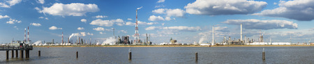 destilacion: Panorama de una gran zona de la refinería con la flama de altura se acumula en el puerto de Amberes, Bélgica, con un montón de torres de destilación. Foto de archivo