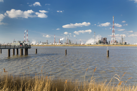destilacion: A large refinery with gas storage tanks in the port of Antwerp, Belgium with lots of distillation towers and a jetty in the foreground.