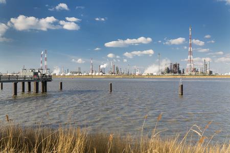 destilacion: Una gran refinería con tanques de almacenamiento de gas en el puerto de Amberes, Bélgica, con un montón de torres de destilación y un embarcadero en el primer plano.