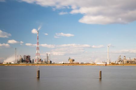 destilacion: Tiro de larga exposici�n de una refiner�a con antorcha de altura en el puerto de Amberes, B�lgica, con un mont�n de torres de destilaci�n.