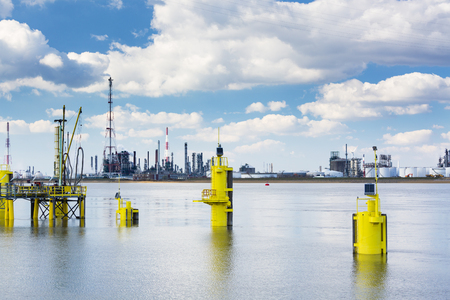 jetty: A large oil refinery with smoke stacks in the port of Antwerp, Belgium with lots of distillation towers and some yellow poles in the foreground.
