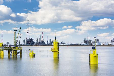destilacion: Una gran refinería de petróleo con pilas de humo en el puerto de Amberes, Bélgica, con un montón de torres de destilación y algunos postes de color amarillo en el primer plano. Foto de archivo