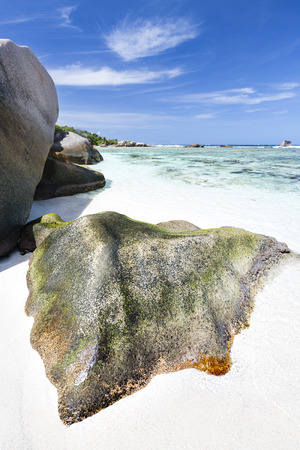 pristine corals: Perfect white beach Anse Pierrot near Source DArgent in La Digue, Seychelles with a colorful granite rock in the foreground