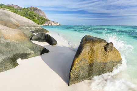 d'argent: A wave splashing over a beautiful granite rock at Anse Source DArgent in La Digue, Seychelles Stock Photo