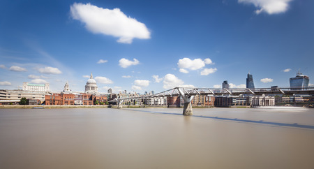 st pauls cathedral: Millennium Bridge in London with St. Pauls Cathedral in the background and a beautiful sky. Long exposure shot. Stock Photo
