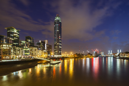 battersea: A skyscraper and modern buildings in the St George Wharf quarter in Vauxhall, London at night with the Battersea Power Station in the background Stock Photo