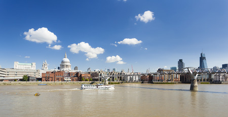 st pauls: Millennium Bridge in London with St. Pauls Cathedral in the background and a boat passing by Stock Photo