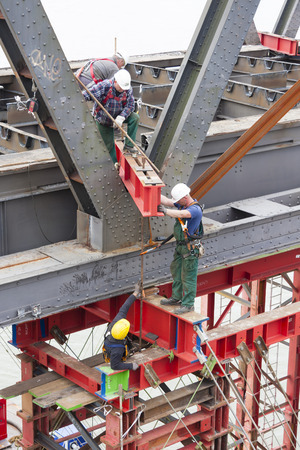 deconstruction: WESEL - SEPTEMBER 6: Several workers attaching an industrial carrying platform to support a bridge deconstruction on Rhine river, Germany on September 6, 2012 Editorial