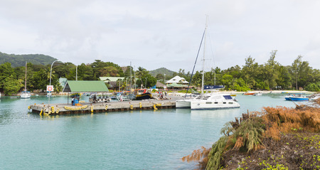 digue: LA DIGUE - AUGUST 09: Boats and people in the harbor of La Digue, Seychelles on August 09, 2014