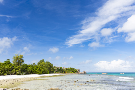 severe: Low tide at Anse Severe in La Digue, Seychelles with palm trees and granite rocks